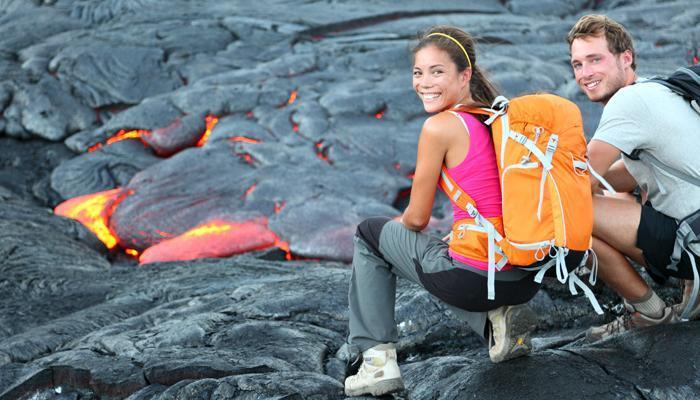 Hawaii lava tourist on hike. Tourists hiking near flowing lava f